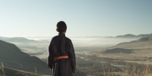 boy in Mongolian mountains looking down in to a valley with a river at sunrise